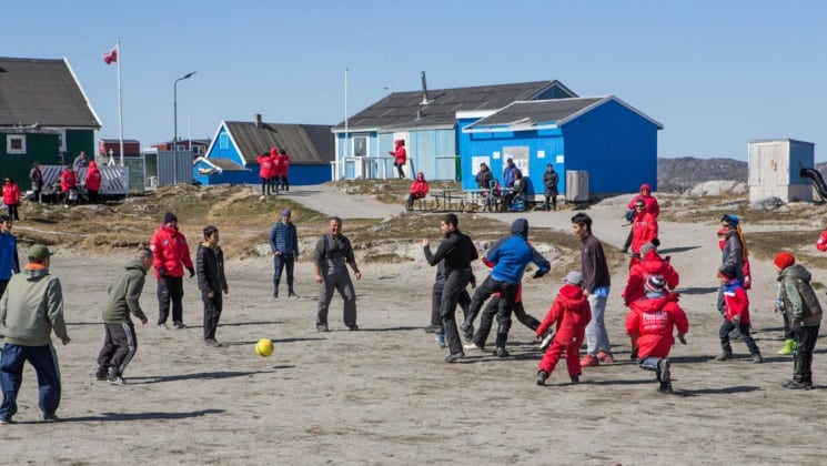 inuit villagers kick a soccer ball in a dirt field in the arctic circle
