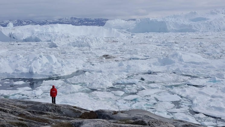a man walks along the tundra with the polar ice sheet in the background in the arctic circle