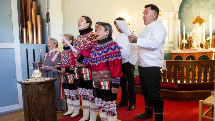 inuit villagers in traditional clothing sing as a choir in the arctic circle