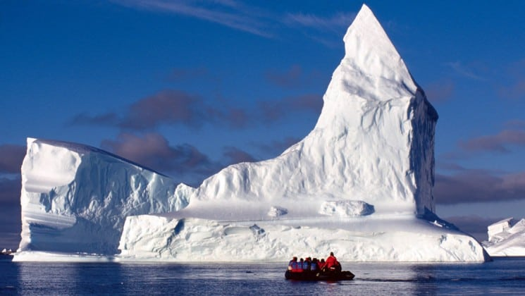 A zodiac full of passengers from the weddell sea emperor penguin voyage cruise motors up to an iceberg in antarctica
