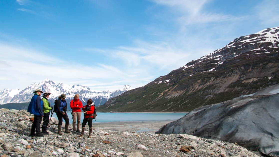 A group of traavelers on a rocky beach in Alaska with cliagial ice and mountains.