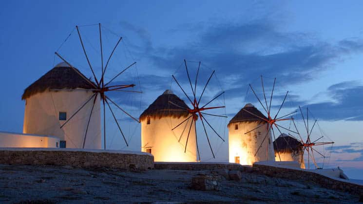 the iconic windmills of mykonos lit up at night