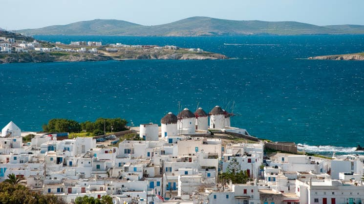 View from a high point on the greek island of mykonos with all of the white buildings and the large windmills by the water