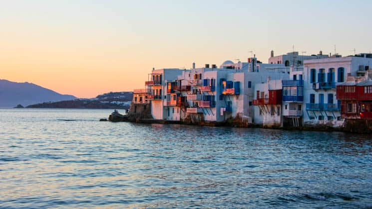 the seaside village of mykonos greece with white buildings and balconies over the water at sunset