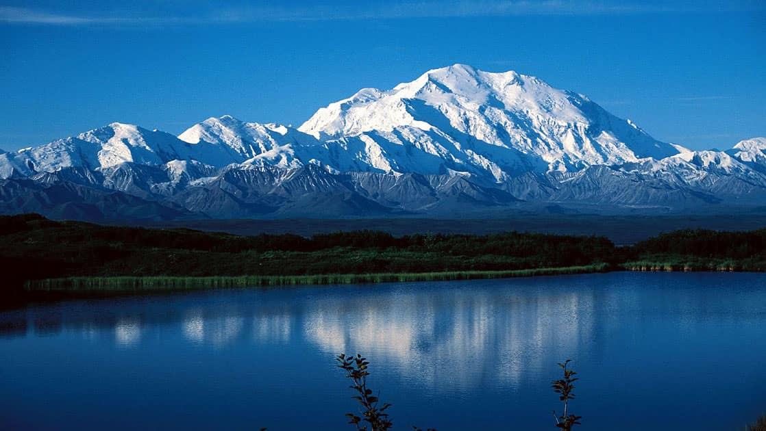 Denali mountain range with snowy peaks and a lake in front