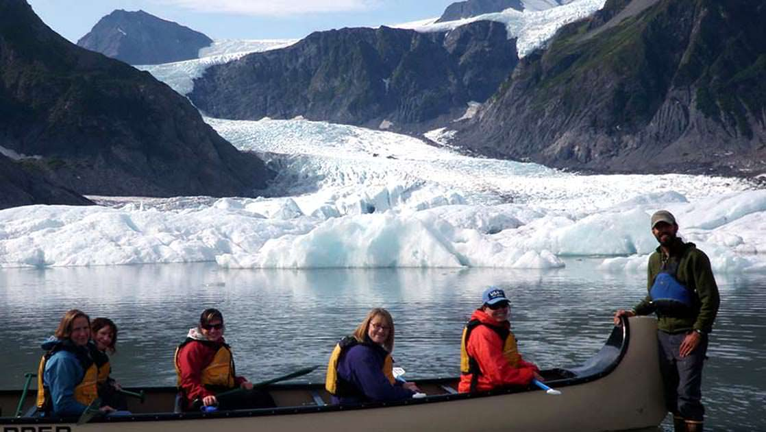 Canoe with passengers smiling in front of the Pedersen Glacier on the Kenai peninsula as their guide is standing in the water with high rubber boots