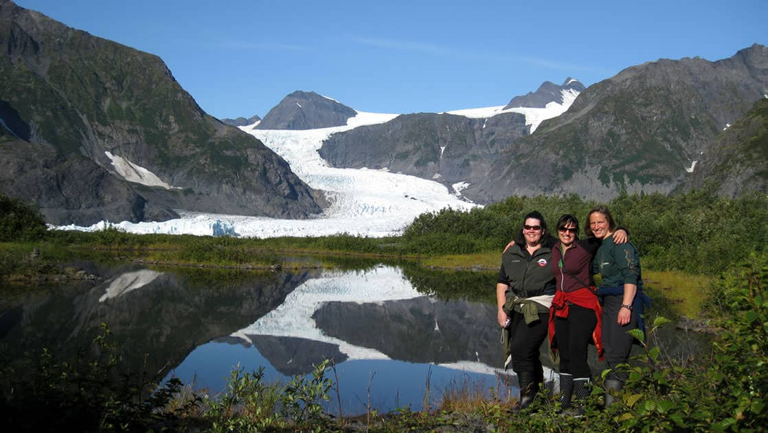 Three woman posing in front of the Pederson glacier with the reflection in the water on the kenai peninsula in alaska