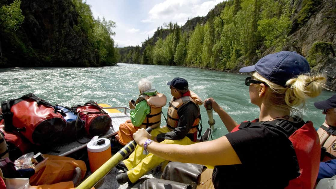 Group of guests on a river rafting excursion in alaska with their guide