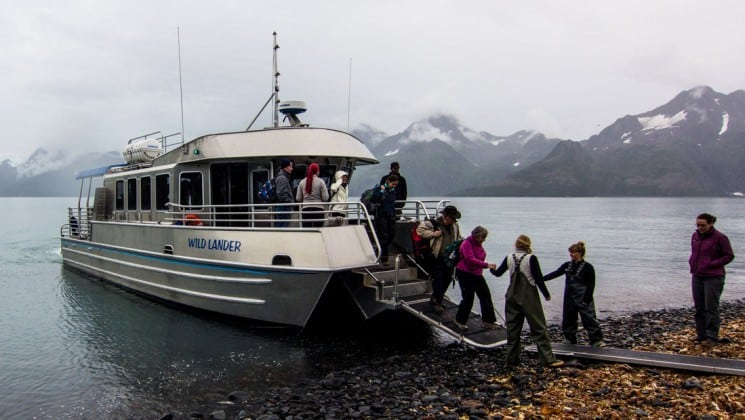 Guest walking down a ramp of their small boat in alaska