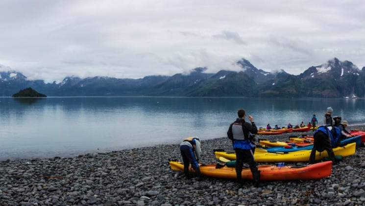 Group of kayaks on the rocky beach along the water on a cloudy and misty day in Alaska