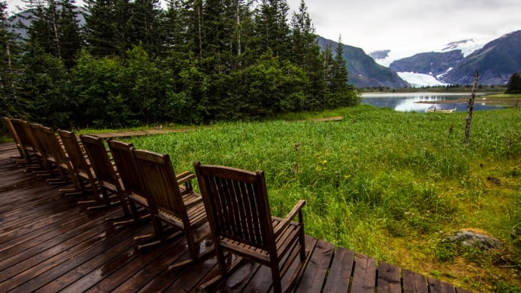 Chairs lined up on the deck facing a glacier across the lagoon in kenai fjords alaska