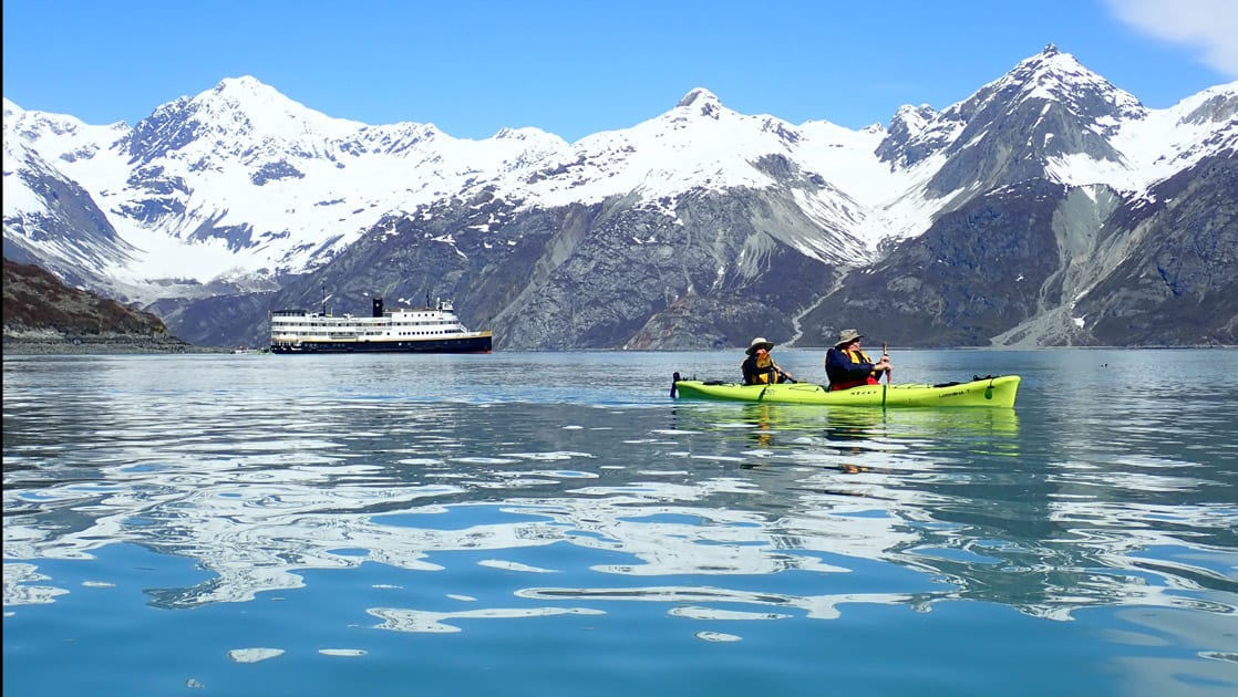 two travelers kayaking inside Glacier Bay National park, the SS Legacy small ship folats behind them and in the background a snowy mountain range