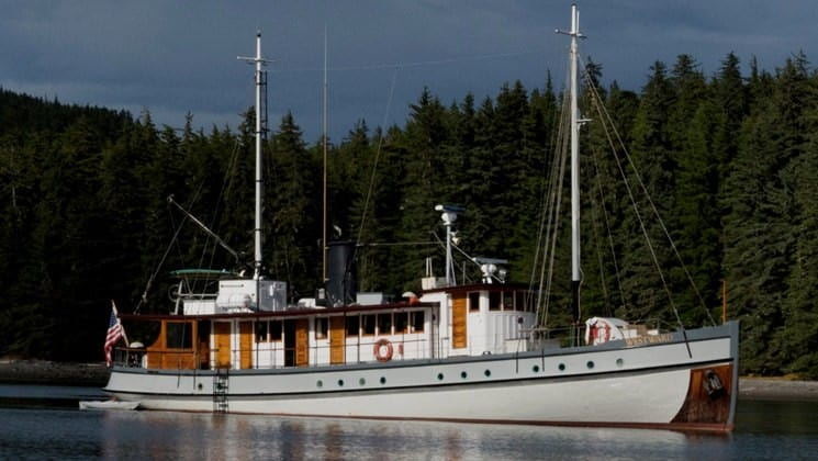 westward alaska small ship anchored on still water with forest behind it
