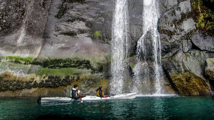 alaska traveler in a kayak on still water sits in front of a sheer rocky cliff with a waterfall coming down it