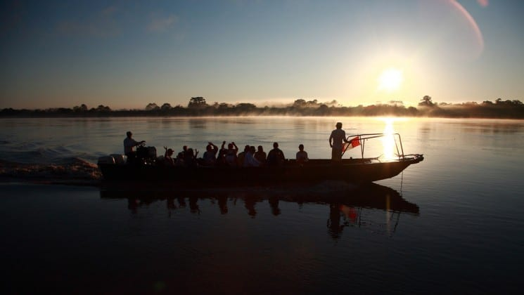 Canoe full of passengers going down a river in the Peruvian Amazon at sunset