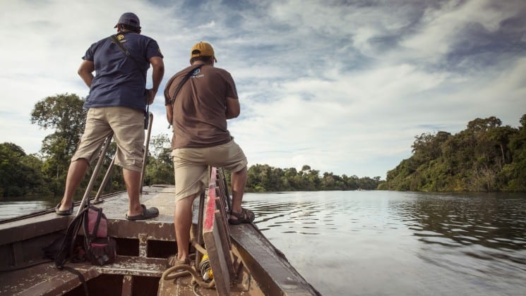 Two men standing at the bow of a small boat looking ahead as they go down a river in the Peruvian Amazon