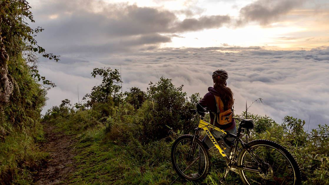 Bike riding activity on an Ecuador land tour. A female guest wearing a helmet stands next to her yellow bicycle at the very top of a lush green trail, lookout out over the endless sea of white clouds