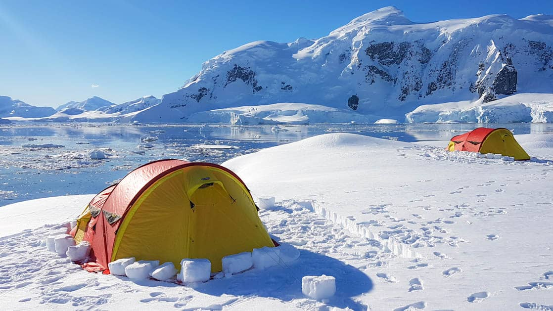 yellow and orange tent set up on the snow in antarctica with a large mountain in the distance