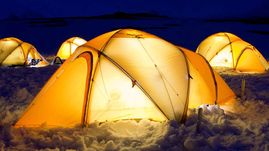illuminated yellow tent at night in antarctica