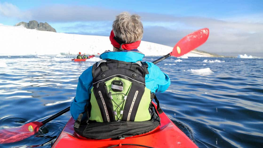 solo traveler kayaking during the antarctic peninsula basecamp expedition cruise on a sunny day