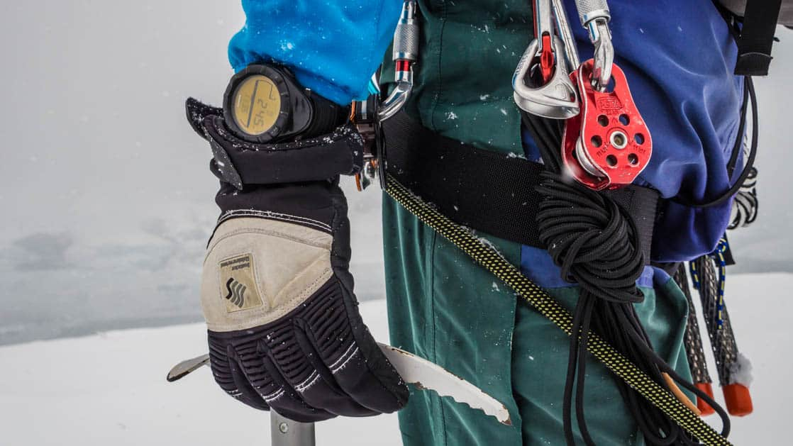 close up of a traveler's gloved hand holding a piece of antarctic mountaineering gear