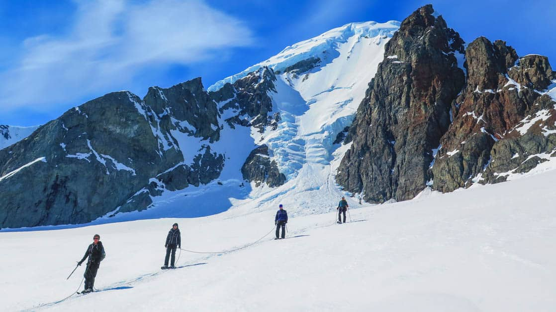 group of adventure travelers walks up a snowy mountain on a sunny day in antarctica