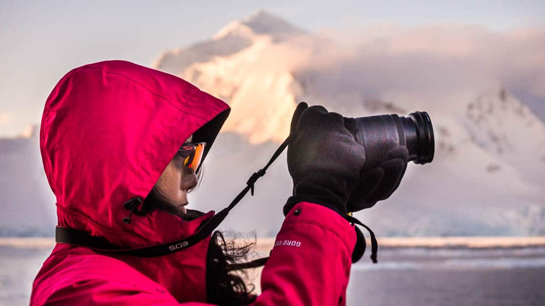 antarctica traveler wearing a pink hooded jacket takes a picture while an illuminated mountain juts out in the distance