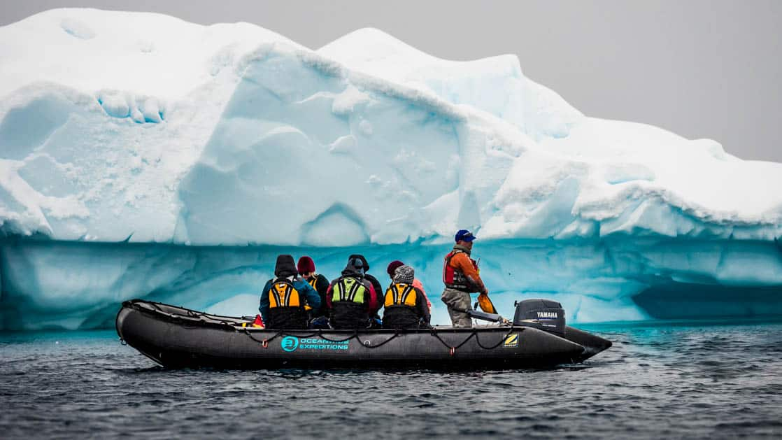 group of travelers in a zodiac skiff looking at a turquoise antarctica icebergy
