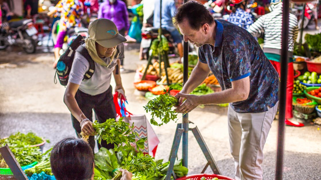 Travelers with chef David Thompson shopping for fruits and vegetables at the local outdoor market.