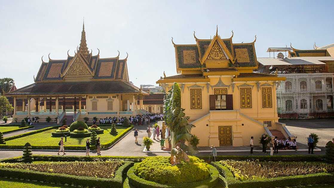 Yellow and elegant Royal Palace with people walking around to explore in Cambodia.