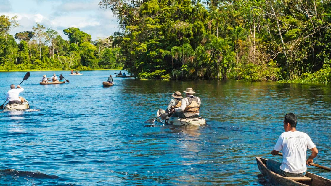 adventure travelers kayaking down teh amazon river with lush green foliage on either side