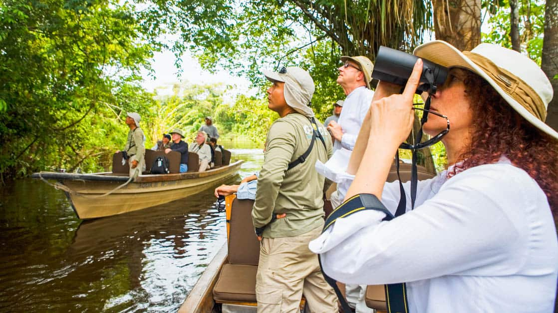 adventure travelers take pictures into the amazonian jungle canopy from small boats