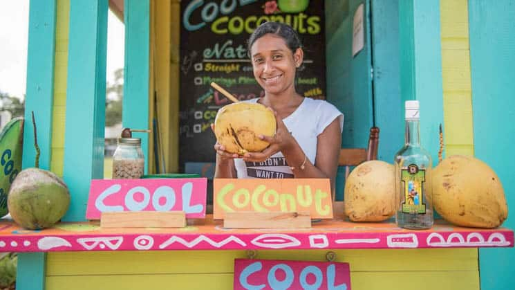 A Belizian shopkeeper selling coconut water with a smile.