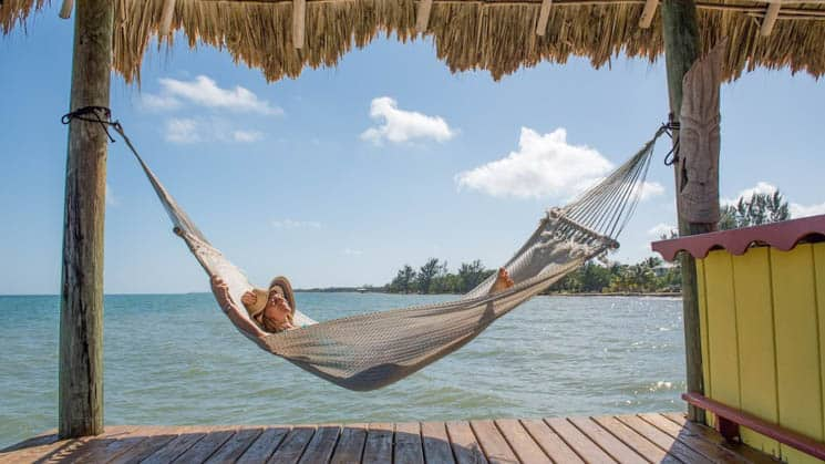 A traveler relaxing in a hammock on a dock with a grass shade.