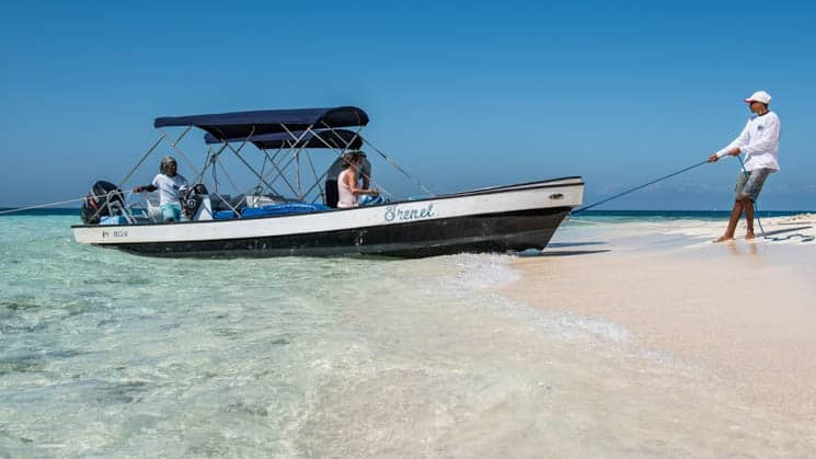 A skiff with travelers being pulled up on a white-sand beach in Belize.