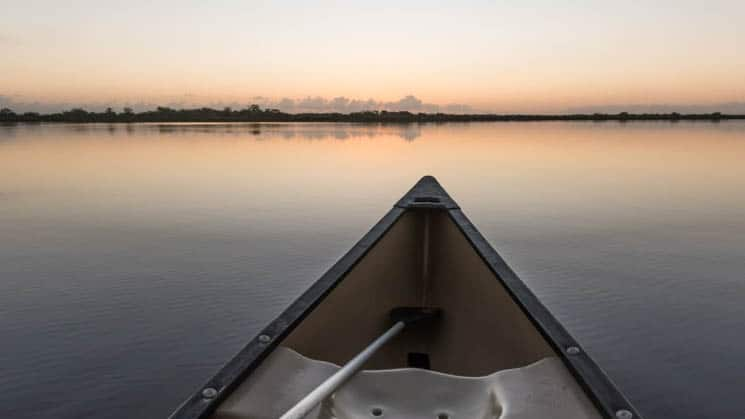 A canoe bow with view of a sunset with pink and orange skies.