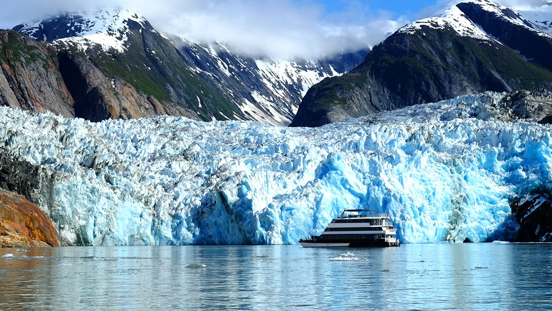 The Alaska small ship the Alaskan Dream floats in the water infront of a massive teal crystal glacier, behind it a snow capped mountain range
