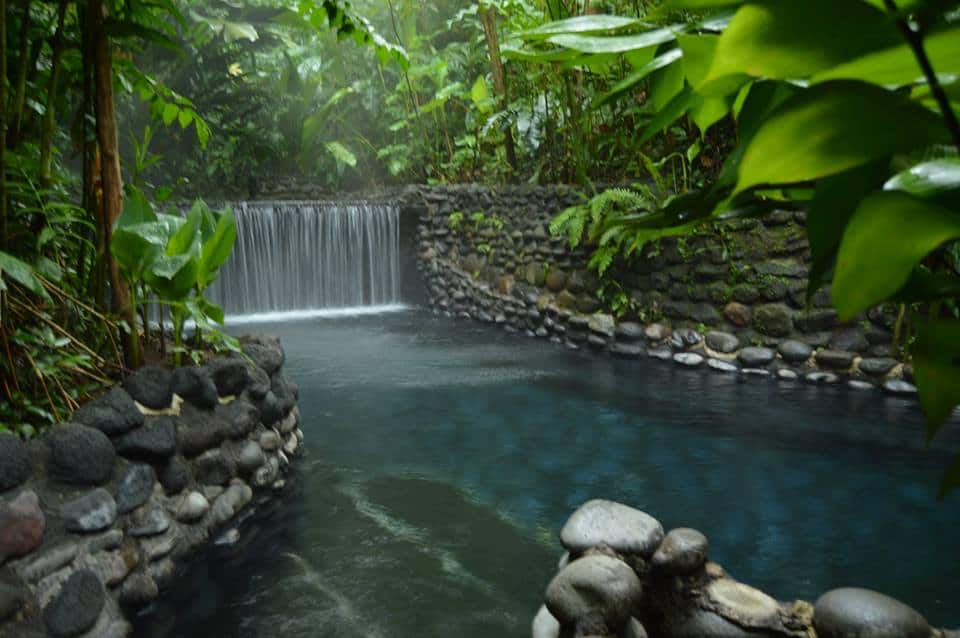 A beautiful blue hot springs with wide, short waterfall falling into the stone surrounded pool.