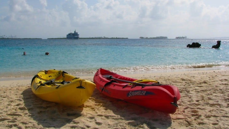 Yellow and red kayaks on white sand beach with blue water on Costa Rica small ship cruise