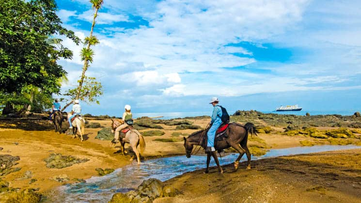travelers horseback riding on a sunny day at a costa rica beach