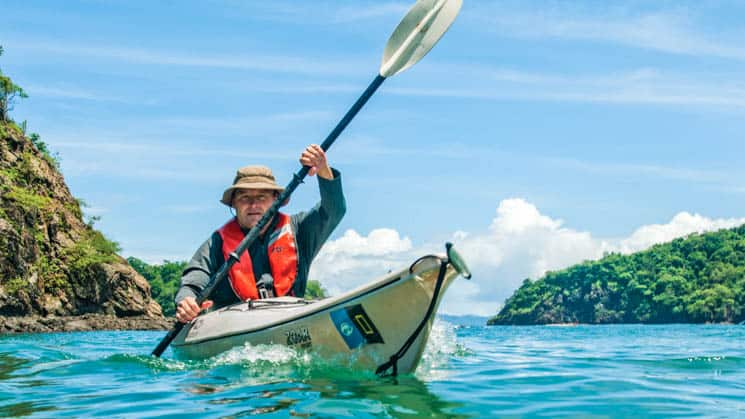 traveler with a red life jacket and hat kayaks on turquoise water on a sunny day next to the costa rica jungle