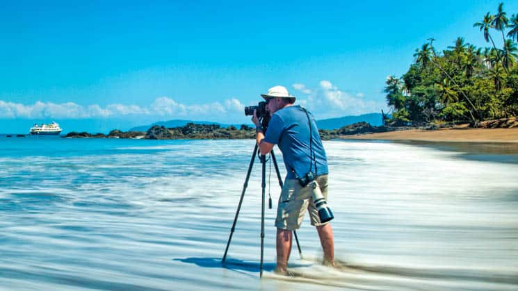 traveler standing in shallow ocean water with a camera on a tripod takes a picture of the national geographic costa rica small ship on a sunny day