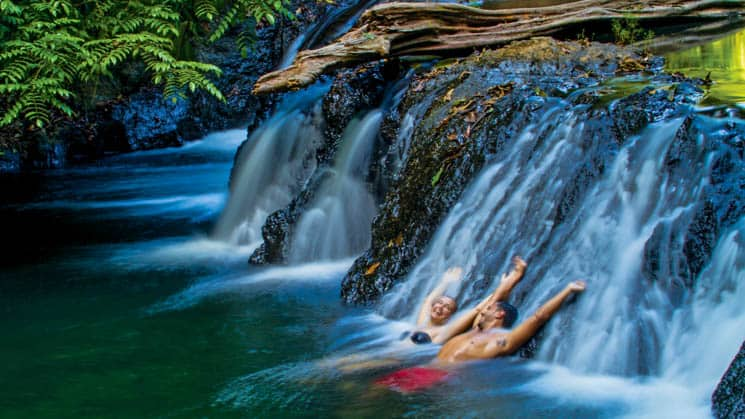 two travelers relax against a rock while water flows over it in the jungle of Corcovado National Park, Costa Rica