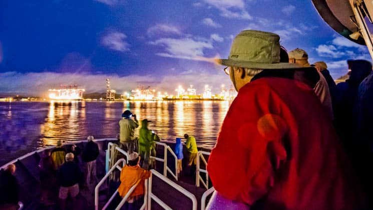 travelers on the bow of a national geographic small ship at night about to go through an illuminated panama canal