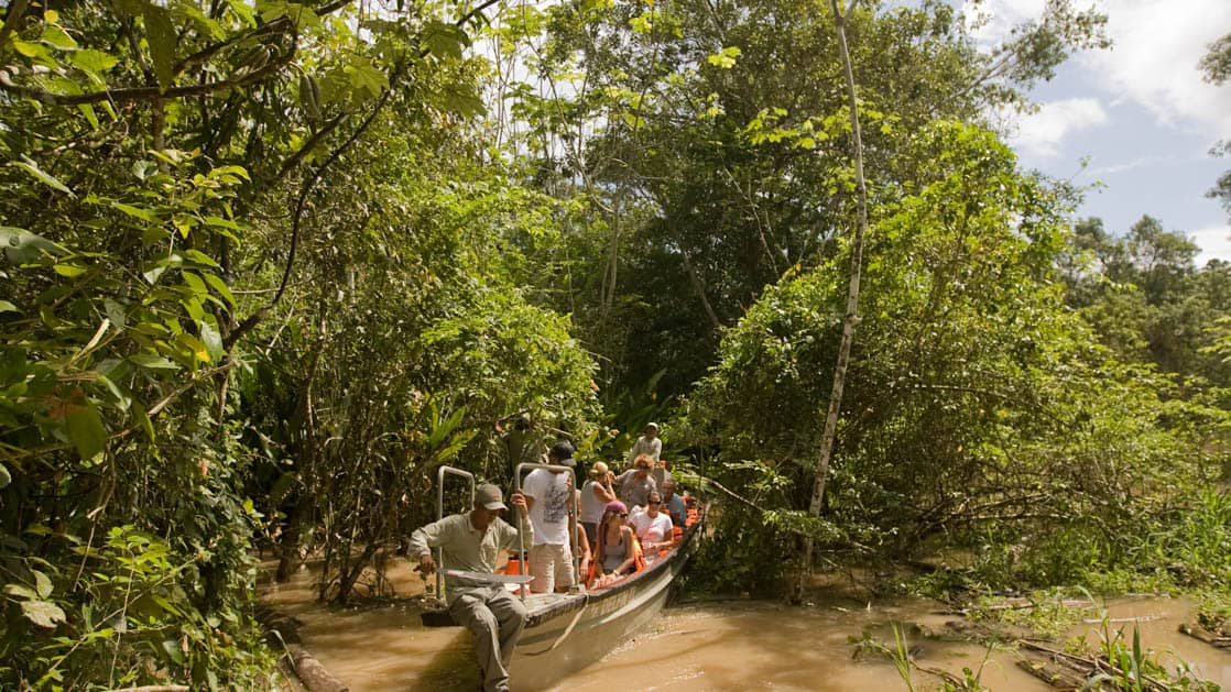 group of adventure travelers and a guide in a skiff deep in the amazon jungle with foliage on all sides of them