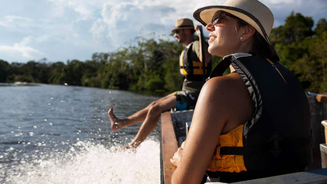female solo traveler in a hat and life jacket looks to the side of a skiff cruising down the amazon river in peru on a sunny day while the guide sits on the front with his feet hanging off
