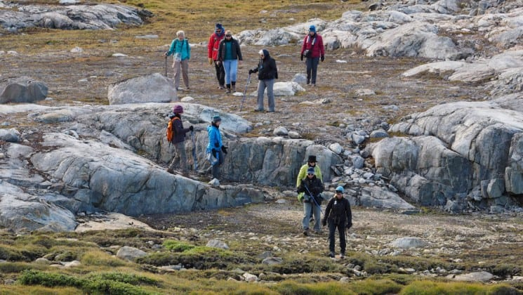 Group of people hiking on the rocky terrain of greenland