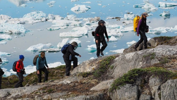 Hikers walking uphill on rocks in greenland with icebergs floating in the water behind them