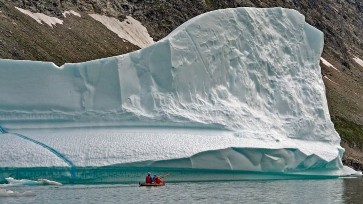 A lone kayaker in greenland dwarfed by a massive iceberg behind