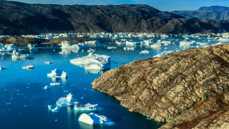 Landscape of greenland with rocky hills and emptiness, except for all of the floating icebergs